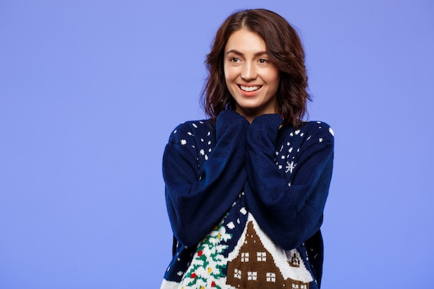 Young cheerful beautiful brunette girl in cosy knitted sweater smiling posing over blue wall