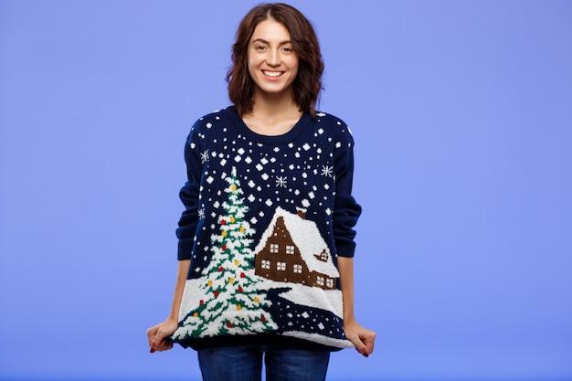 Giovane bella ragazza castana allegra in maglione tricottato accogliente che posa sopra la parete blu