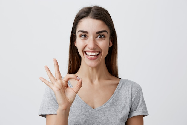 Young cheerful beautiful caucasian girl with dark long hair in casual gray shirt smiling with teeth, making ok sign with fingers,  with happy and excited face expression. copy space.
