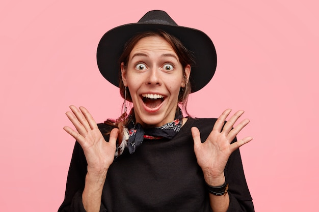 Young cheerful beautiful woman in cowboy style clasps hands and looks with surpisement, sees something amazing, wears hat, has appealing look, isolated over pink wall