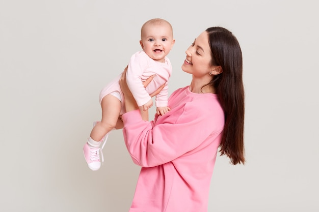 Young cheerful beautiful woman holding baby boy in her hands and looking at her with love, excited toddler girl wearing bodysuit looks at camera, family posing isolated over white wall.