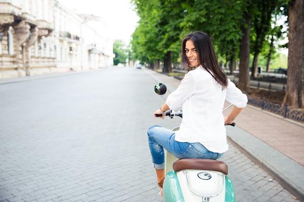 スクーターに乗ってカメラを振り返る若い陽気な美しい女性