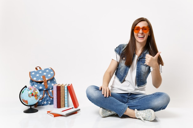 Young cheerful beautiful woman student in red heart glasses showing thumb up sitting near globe backpack school books isolated