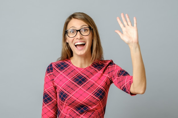 Young cheerful beautiful woman waiving saying hello