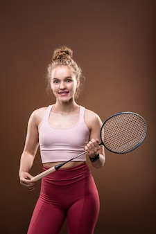 Young cheerful blond female tennis player in pink tanktop and crimson leggins holding racket