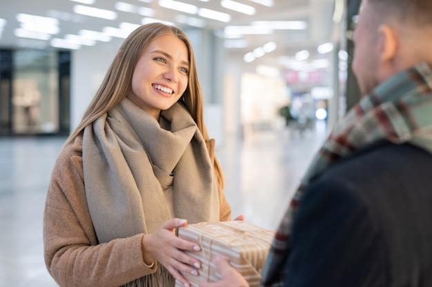 若い陽気なブロンドの女性が彼を見て、ギフトボックスを取って彼女の夫に感謝