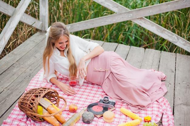 ヴィンテージの服の若い陽気なブロンドの女性は木製の桟橋でピクニックテーブルクロスにある間赤ワインを飲む