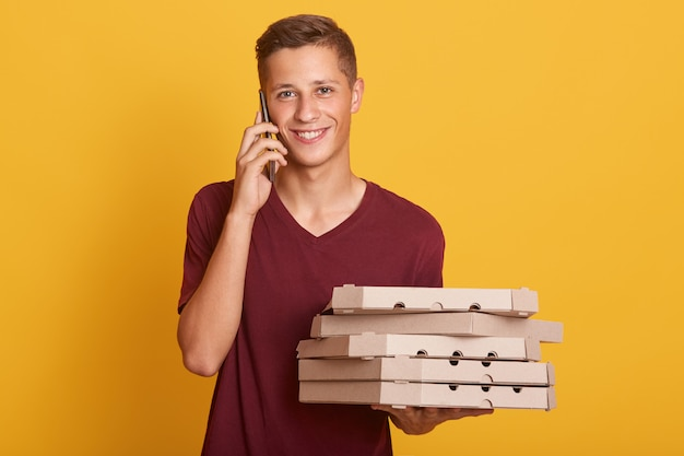 Young cheerful boy standing isolated on yellow in studio, holding cardboard boxes with pizza and smartphone in hands, having conversation, talking on phone, looking directly at camera.