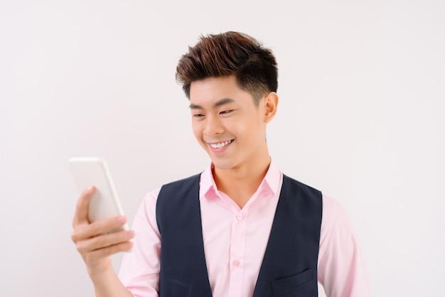 若い陽気なbrunete弁護士は、彼の携帯電話でインターネット上の良いニュースを読んで、純粋な水色の背景に立って笑っています