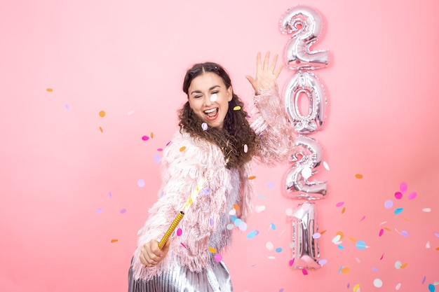 Young cheerful brunette girl with curly hair in a festive dress with a fireworks candle in her hand on a pink wall with silver balloons for the new year concept