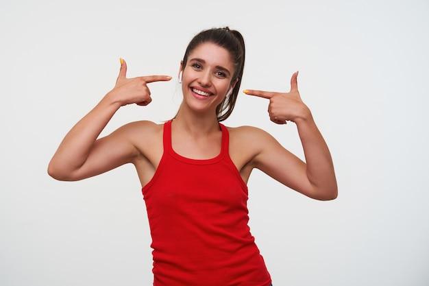 若い陽気なブルネットの女性は赤いtシャツを着て、カメラを見て、広く笑顔で、クールな歌を聞いて、指でヘッドフォンを指して、白い背景の上に立っています。