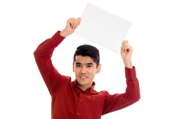 Молодой веселый брюнетка в красной футболке позирует с белым плакатом на стене