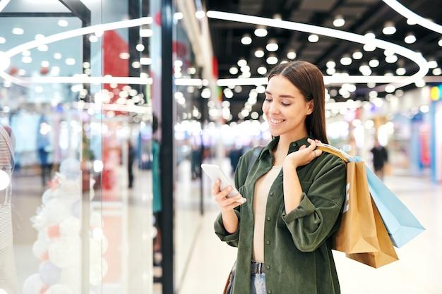 종이 봉지가 스마트 폰에서 스크롤하거나 쇼핑몰에서 쇼핑하는 동안 메시지 또는 광고를 통해보고있는 젊은 쾌활한 갈색 머리 구매자