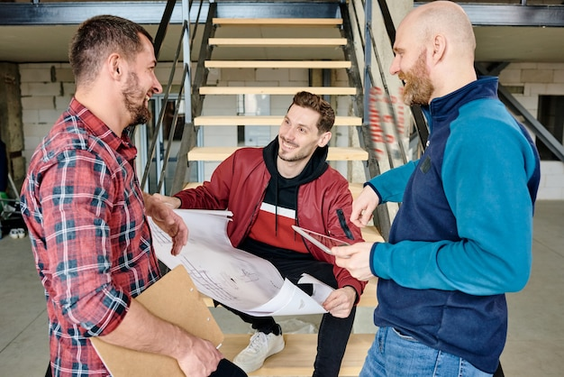 Young cheerful builder with blueprint of sketch sitting on step of staircase and discussing it with colleagues at working meeting
