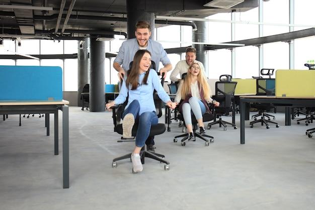 オフィスの椅子でレースをしたり、笑顔で楽しんでいるスマートカジュアルウェアの若い陽気なビジネスマン。