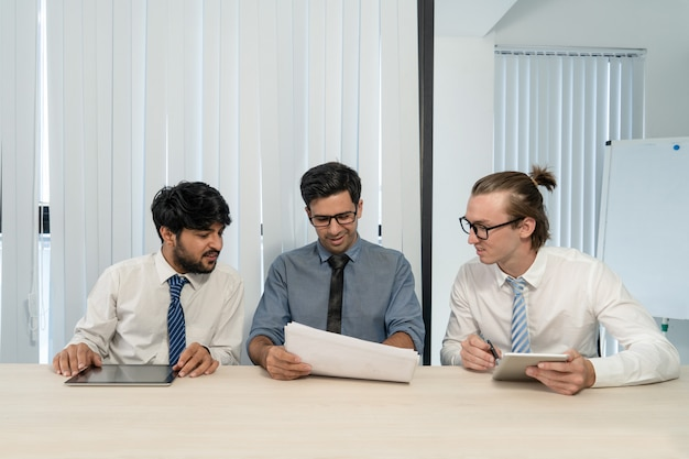 Young cheerful business team reading terms of contract.