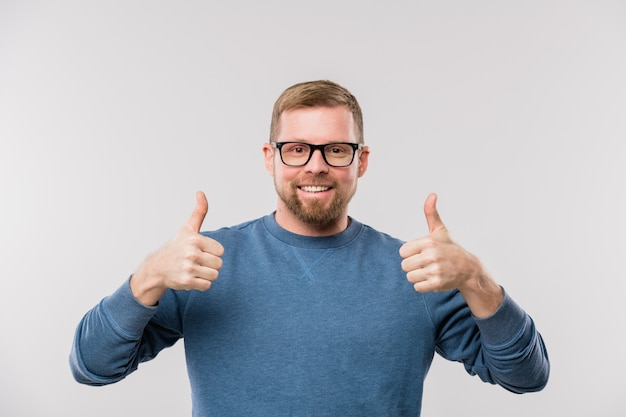 Young cheerful businessman in blue pullover showing thumbs up while standing in front of camera in isolation