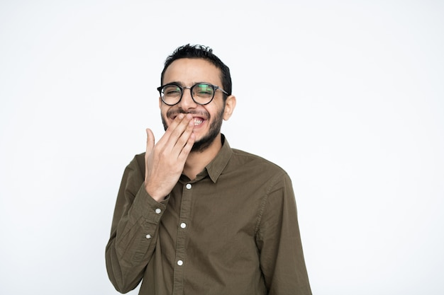 Young cheerful businessman in eyeglasses covering his mouth while laughing at something in front of camera