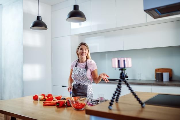 Молодая веселая кавказская белокурая молодая домохозяйка в фартуке держит кухонный нож, готовит здоровую еду и имеет видеозвонок по смартфону, стоя на кухне.