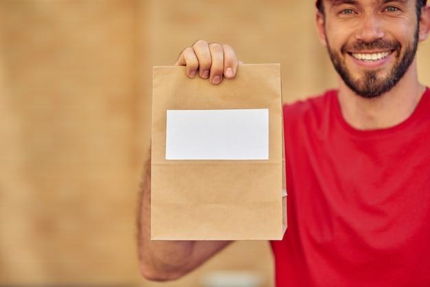 복사 공간이 있는 작은 종이 가방을 들고 빨간색 제복을 입은 젊은 쾌활한 백인 남성 택배