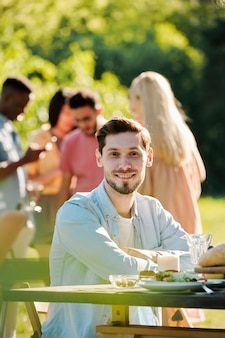 Young cheerful caucasian man in casualwear sitting by served table outdoors while his friends cooking barbecue together