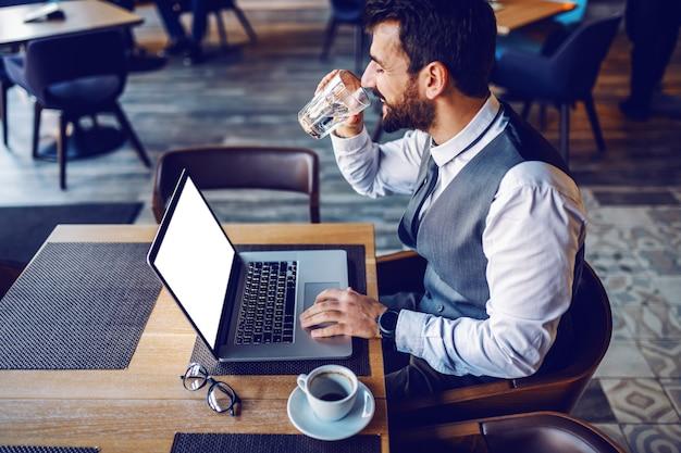 若い陽気な白人成功したひげを生やしたビジネスマンがカフェに座って、ラップトップを使用してオンラインデートと水を飲んでいます。