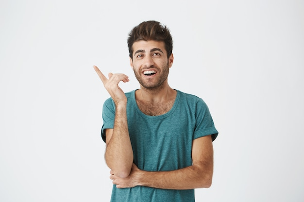 Young cheerful caucasian unshaven guy in casual t-shirt, looking really happy after remembering about day off work tomorrow.