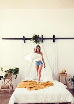 Young cheerful caucasian woman jumping on bed