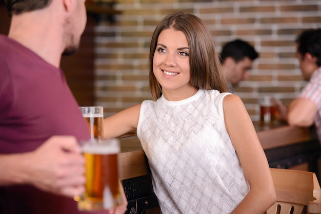 Young cheerful couple drinking beer at the bar.