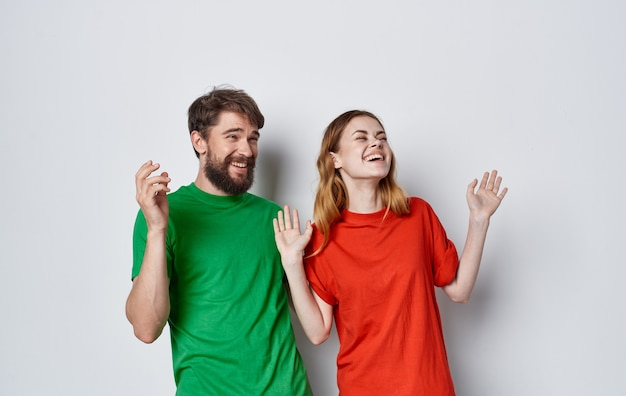 Young cheerful couple emotions multicolored t-shirts studio isolated background. high quality photo