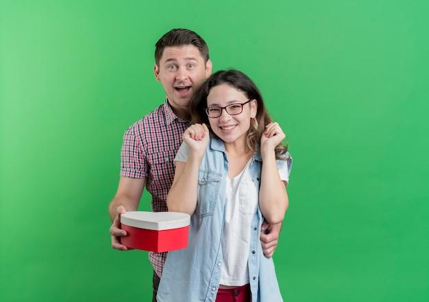 Uomo felice delle giovani coppie allegre che gigving un contenitore di regalo alla sua amica sorridente sorpresa sopra verde