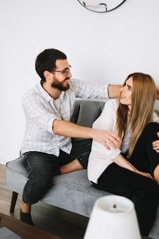 自宅のソファで楽しく抱き合って抱き合う若い陽気なカップル。