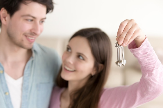 Young cheerful couple holding new house keys