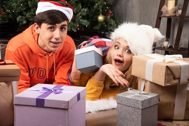 リビングルームでクリスマスの贈り物でポーズをとる愛の若い陽気なカップル。