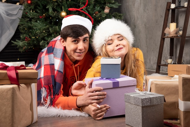 Молодая веселая влюбленная пара позирует с подарками на рождество в гостиной.