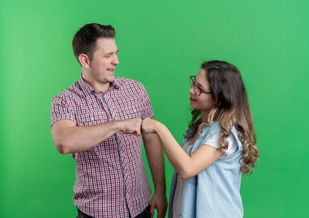 Young cheerful couple man and woman giving fist bump looking at each other making a deal over green