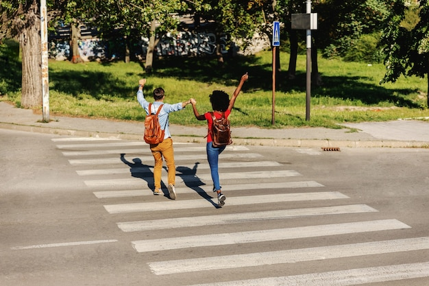 Young cheerful couple running over street and smiling.