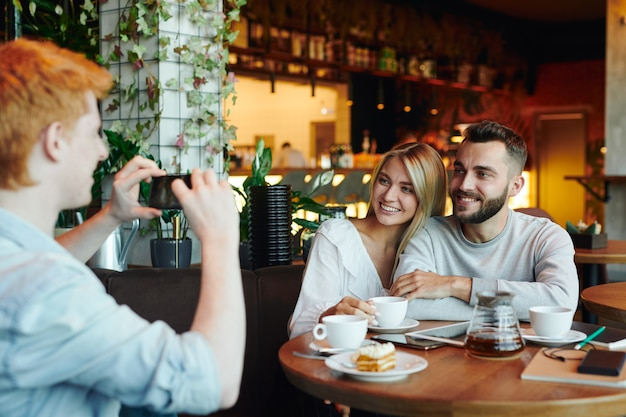 Young cheerful couple sitting by table in cafe and posing for their college friend taking photo of them on smartphone camera