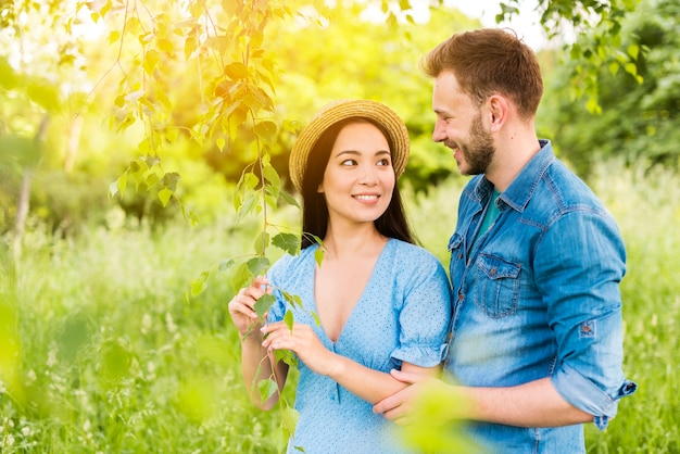 Young cheerful couple smiling at each other with love in nature