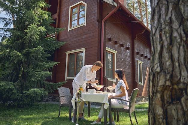 식탁에서 함께 시골에서 시간을 보내는 젊은 명랑 커플