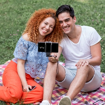 Young and cheerful couple taking selfies
