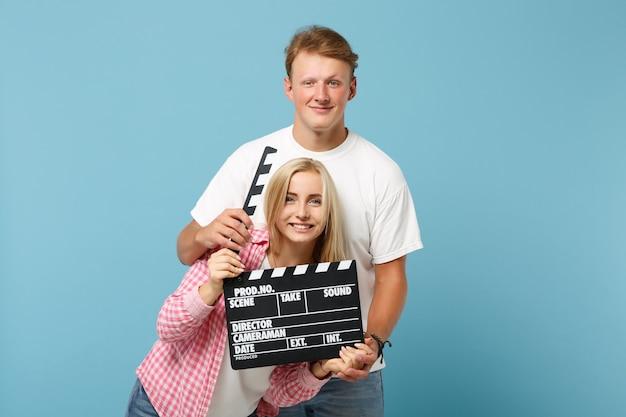 Молодая веселая пара, двое друзей, парень и женщина в белых розовых футболках, позируют