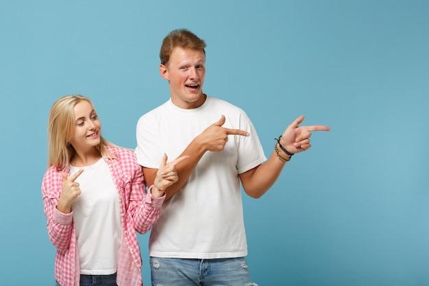 Giovane coppia allegra due amici ragazzo ragazza in bianco rosa vuoto design t-shirt in bianco in posa