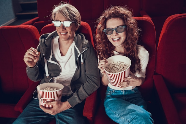Young cheerful couple watching comedy in movie theater.