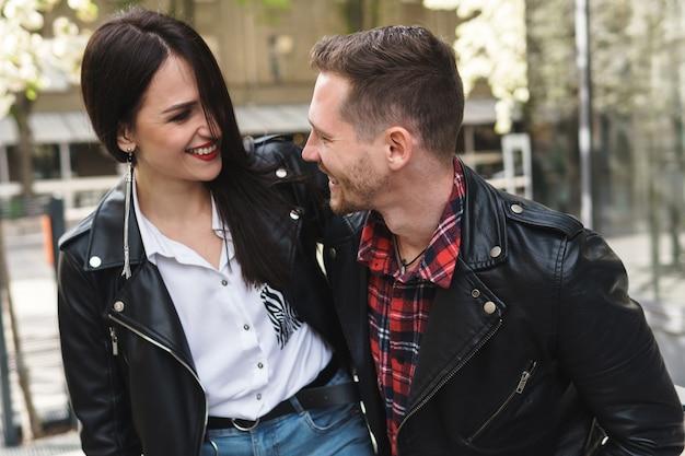 야외에서 데이트하는 동안 가죽 자켓을 입고 젊은 명랑 커플