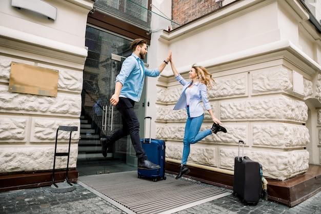 Молодая веселая пара с чемоданами прыгает и дает пять, развлекаясь, до приезда в гостиницу.