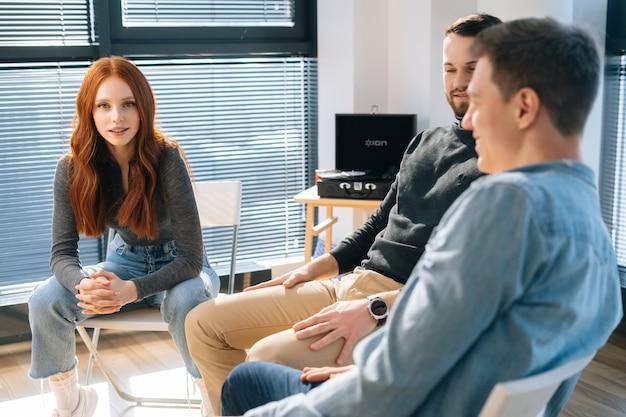 젊고 쾌활한 동료들이 의자에 앉아 일이나 개인적인 문제를 함께 토론합니다.