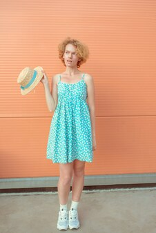 Young cheerful curly redhead woman in blue sundress holding straw hat in her hand on beige backgroun