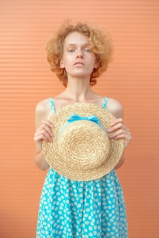 Young cheerful curly redhead woman in blue sundress holding straw hat in her hand on beige