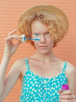 青いサンドレスとベージュの背景に泡と麦わら帽子の若い陽気な巻き毛の赤毛の女性